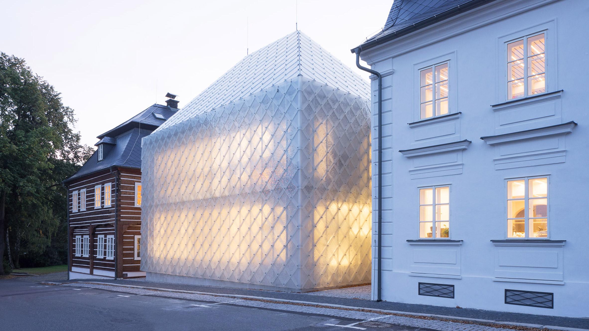 Translucent glass house built alongside historic buildings for Lasvit's Czech Republic HQ