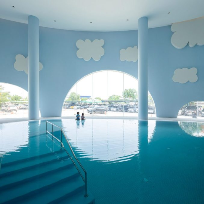 Blue indoor swimming pool with arches and clouds in children's hospital designed by Integrated Field