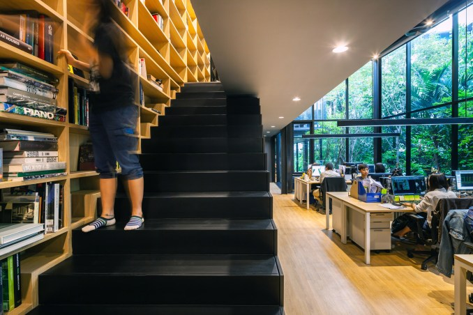 A bookshelf and staircase inside IDIN Architects Office in Bangkok, Thailand