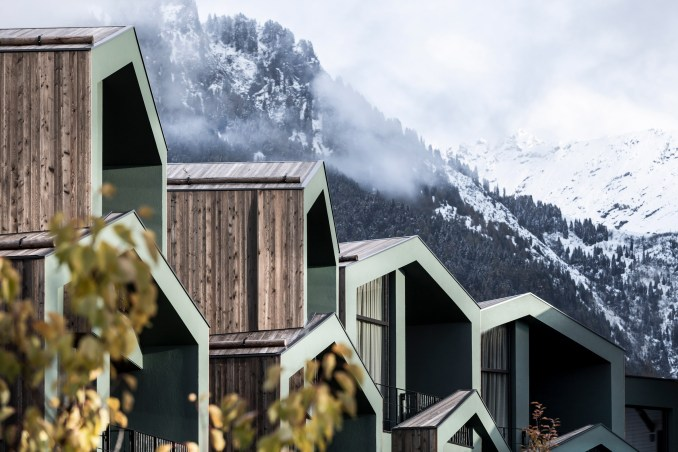 Wood clad and green painted structures against mountain