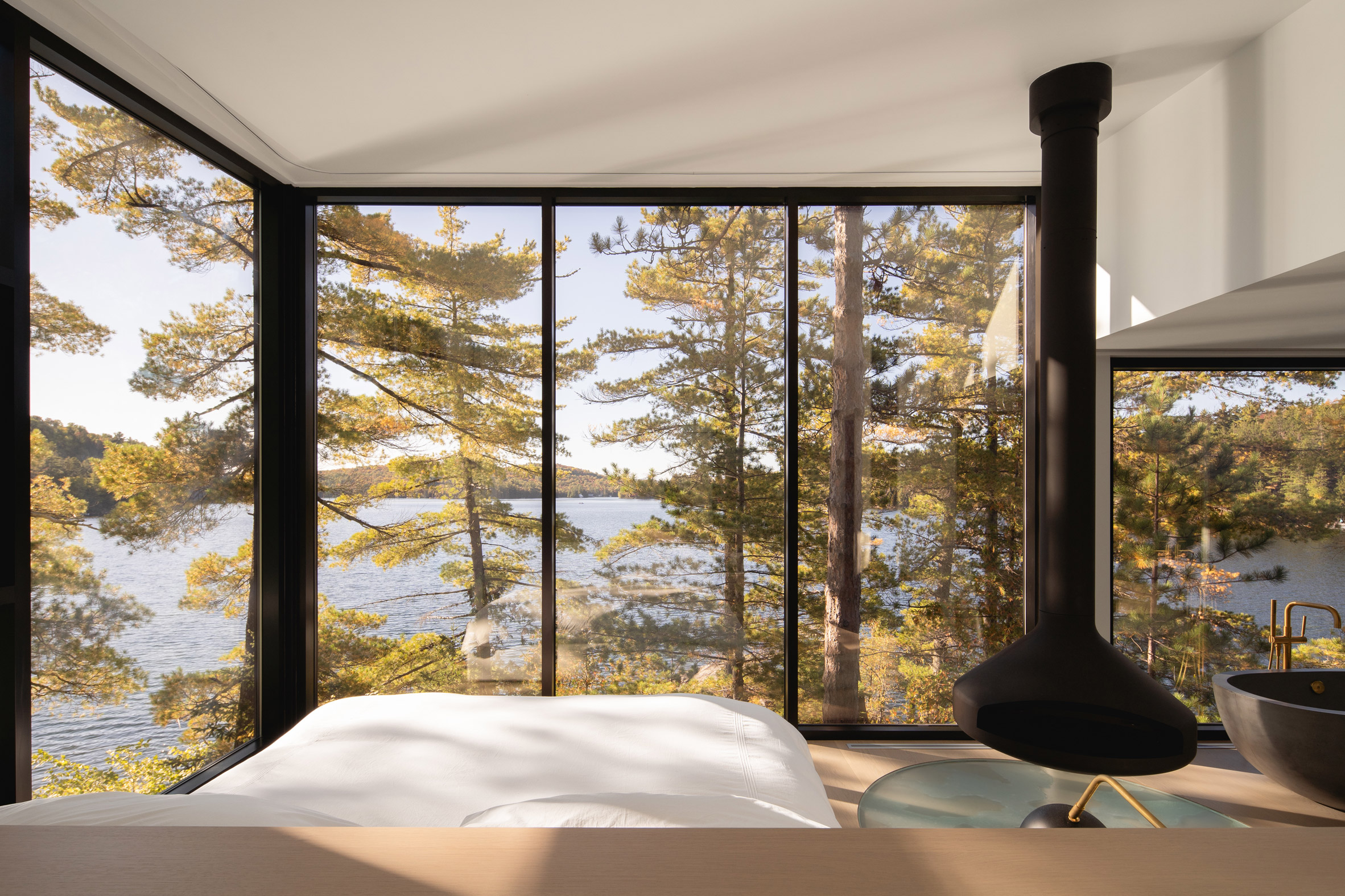 Bedroom with fireplace and bath in Candian lake house