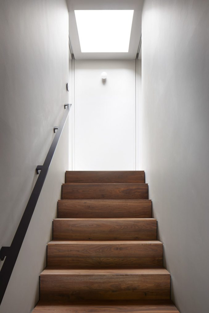 A walnut staircase lit by a skylight in a Scottish house