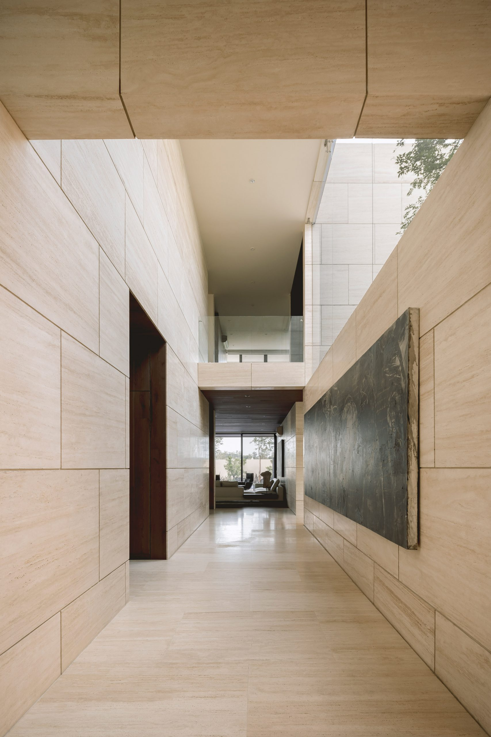 Travertine walls and art inside Casa ZTG by 1540 Arquitectura