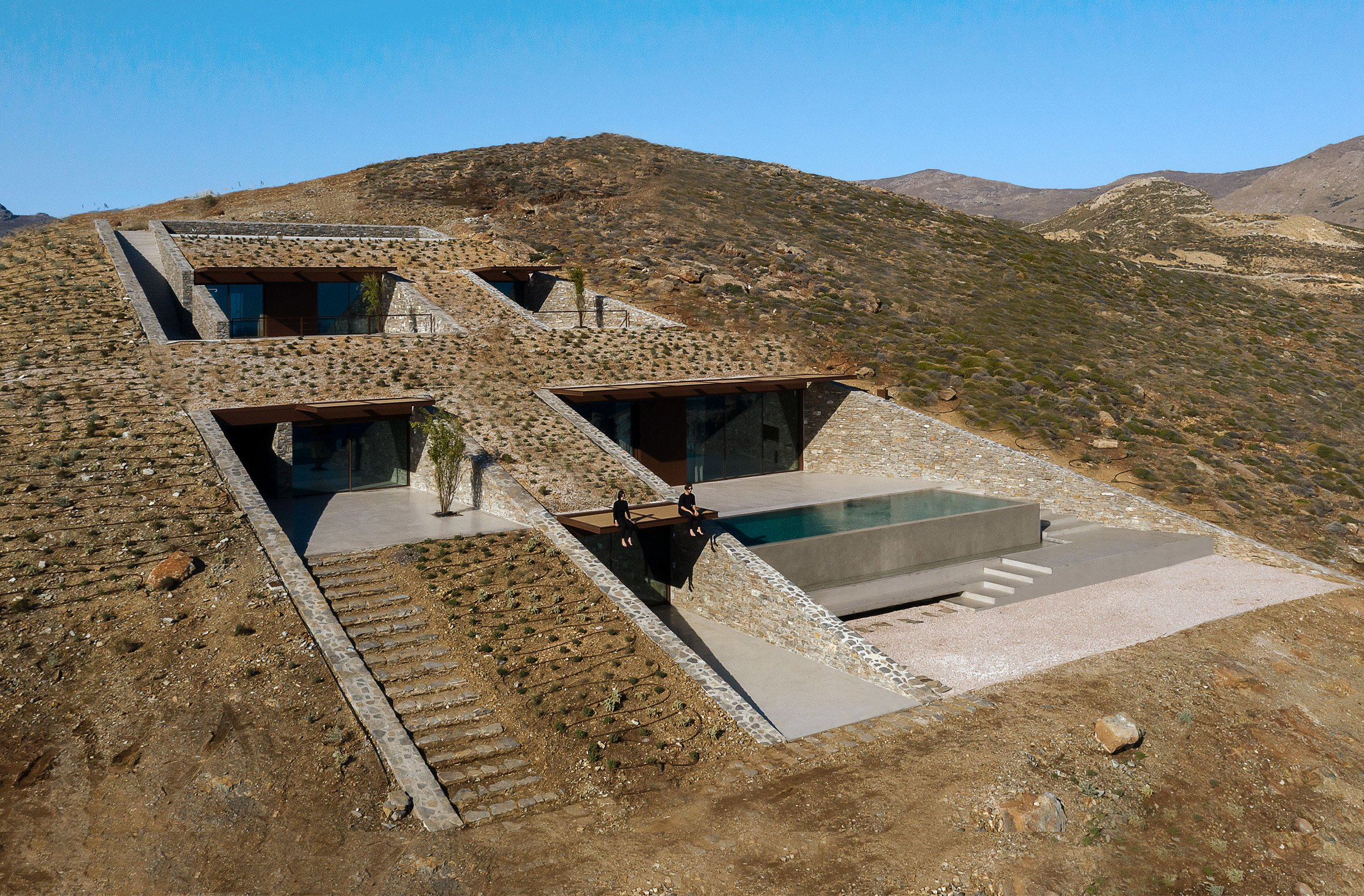 View of different cave-like spaces cut into the hillside by Mold Architects