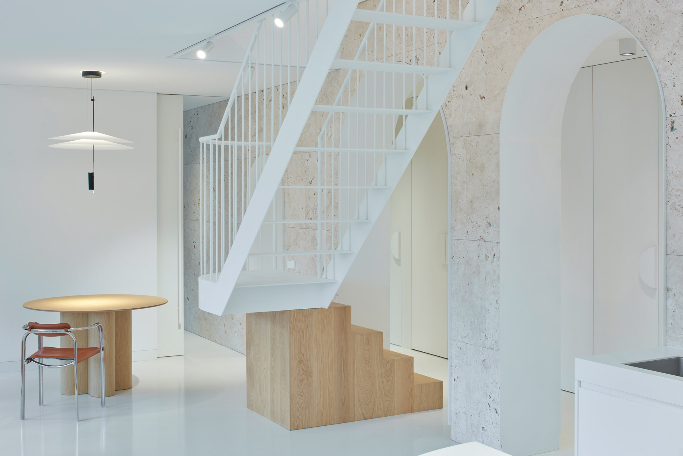 Ground floor of Vilnius apartment by 2XJ with travertine wall and wood and steel staircase