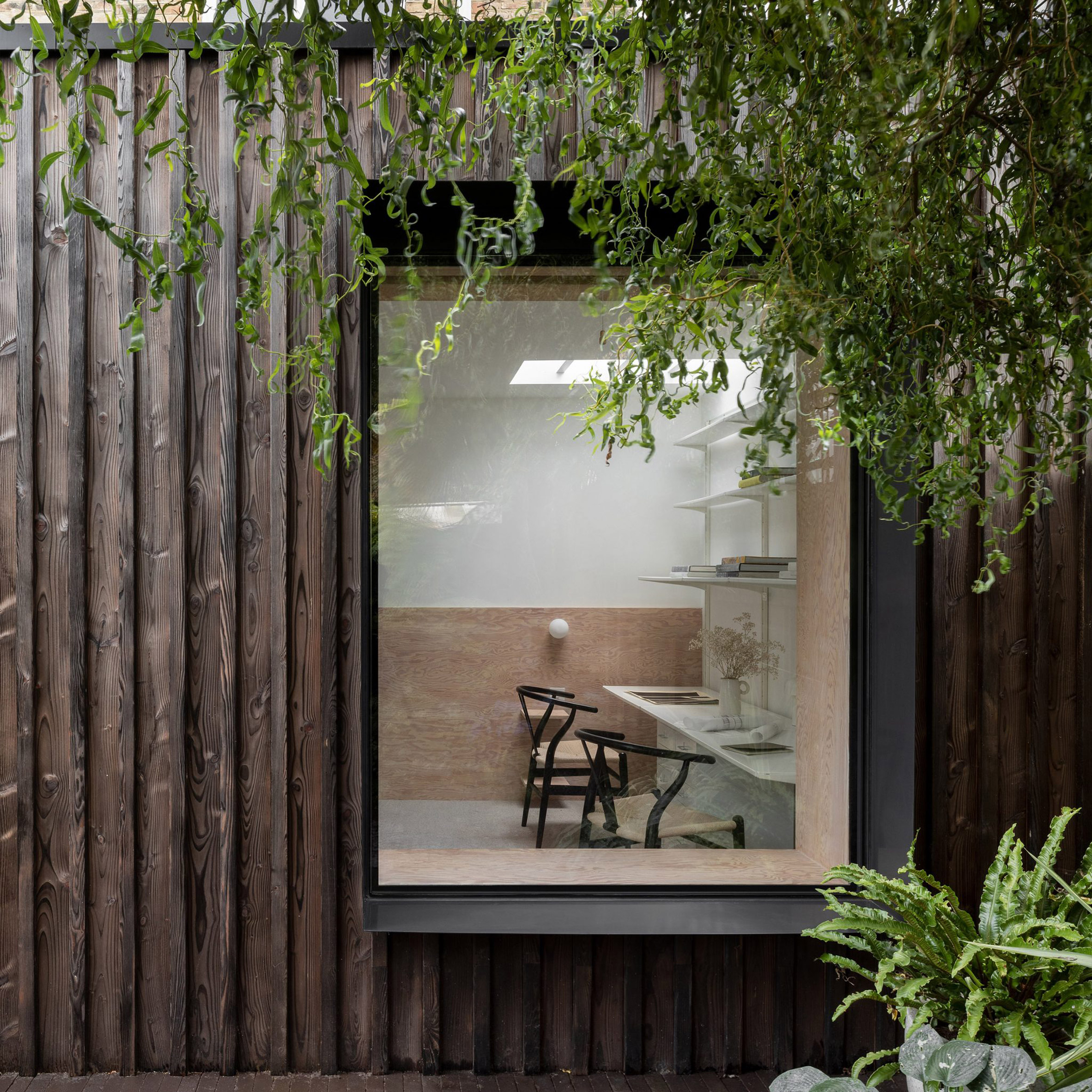 A charred-wood extension with a large window
