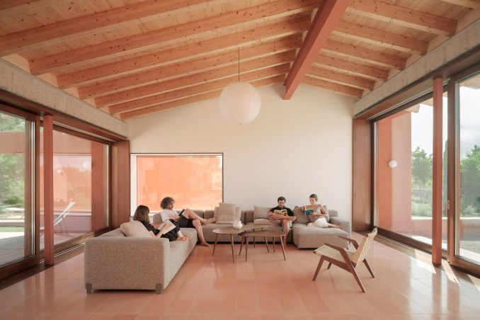 A living room with an exposed wood ceiling and pink floor tiles