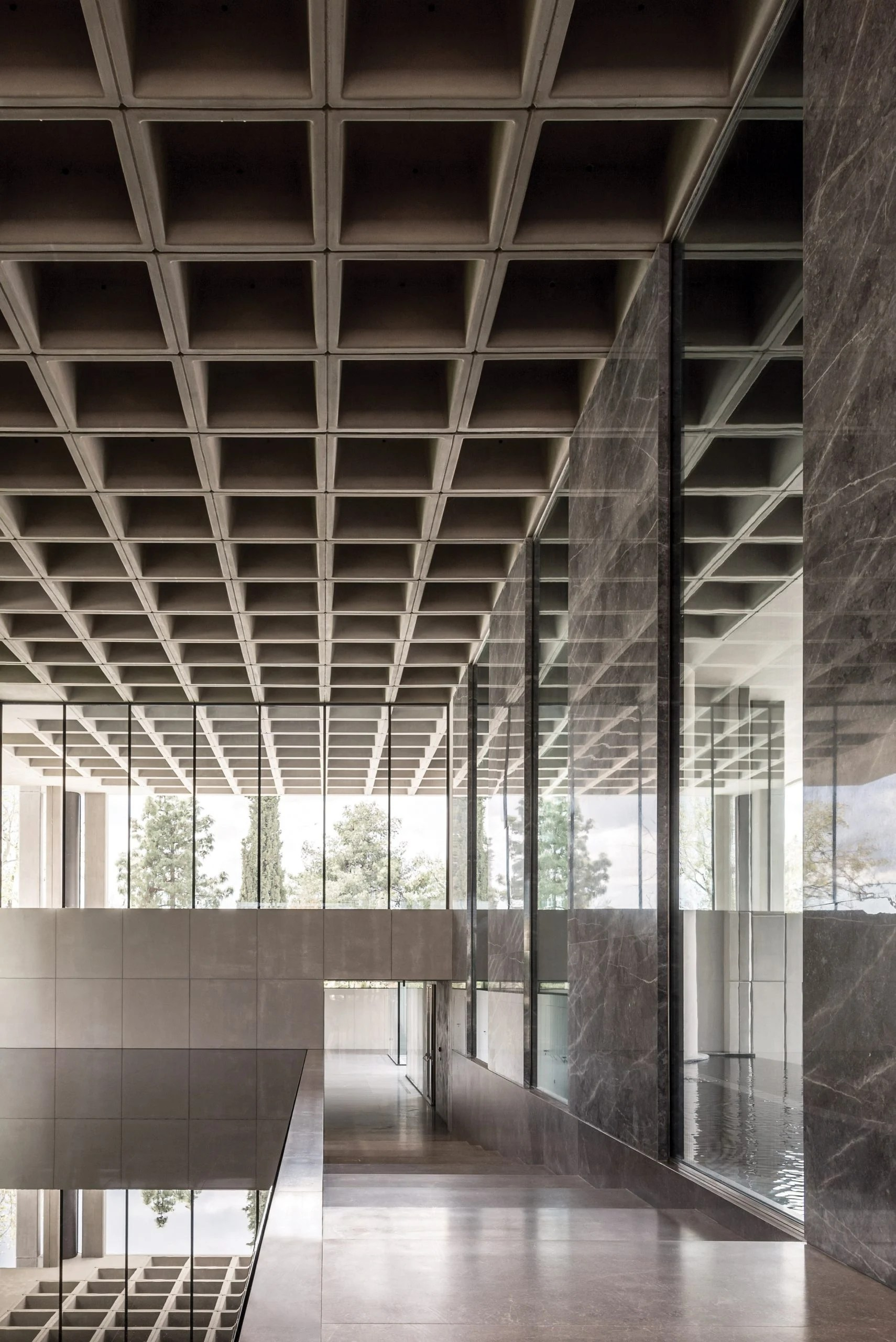 A brutalist office entrance with a waffle slab ceiling
