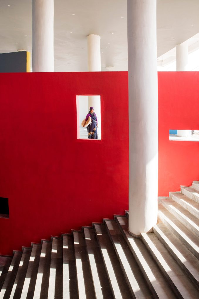 An external staircase lined with a bright red wall