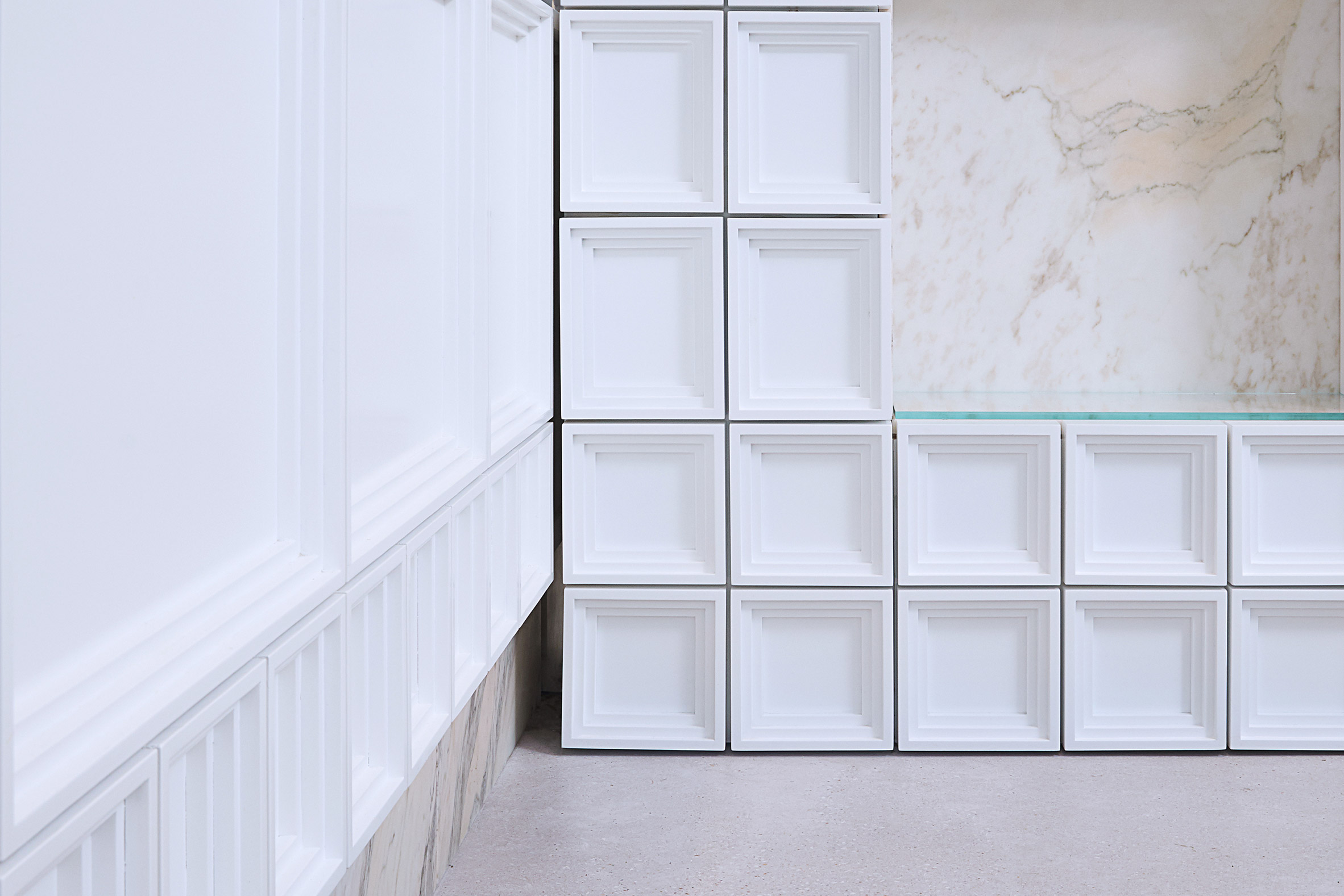 White MFF blocks form storage wall in tea shop by Raams Architecture Studio