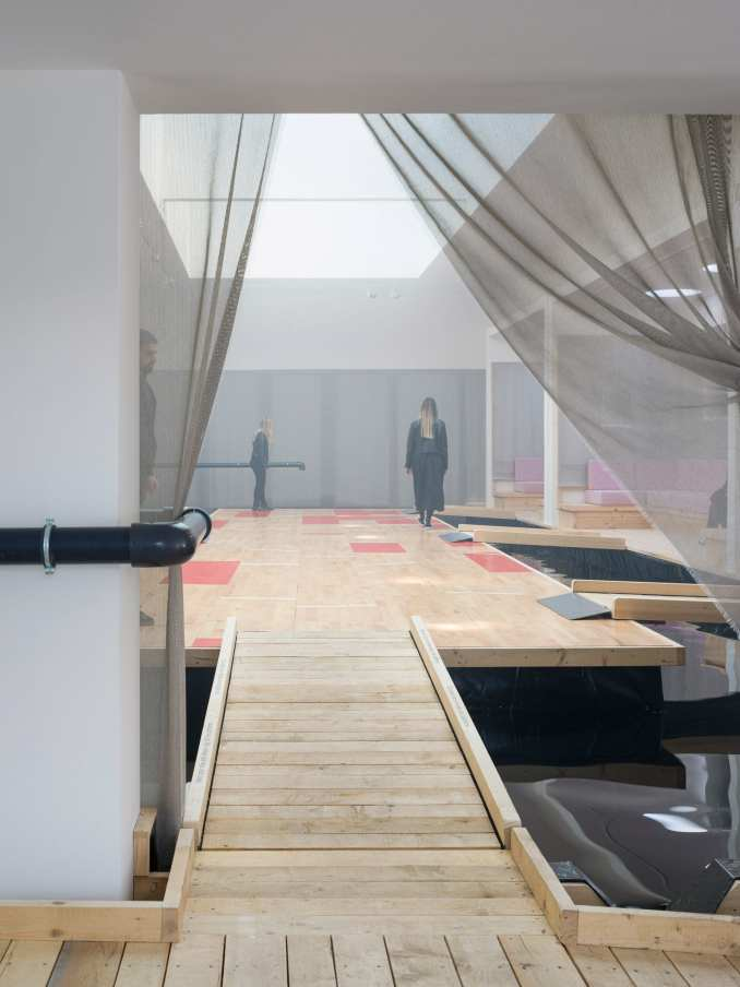 A pine footbridge floats above a flooded room at the Danish Pavilion