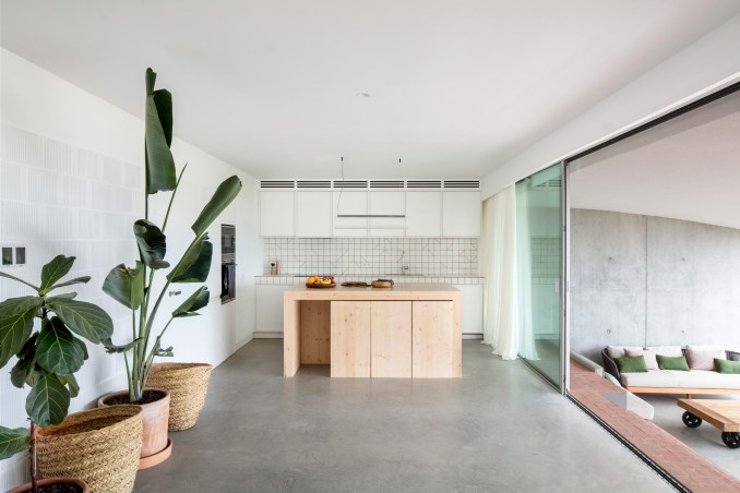 Glass sliding doors at Curved House lead to the outdoors