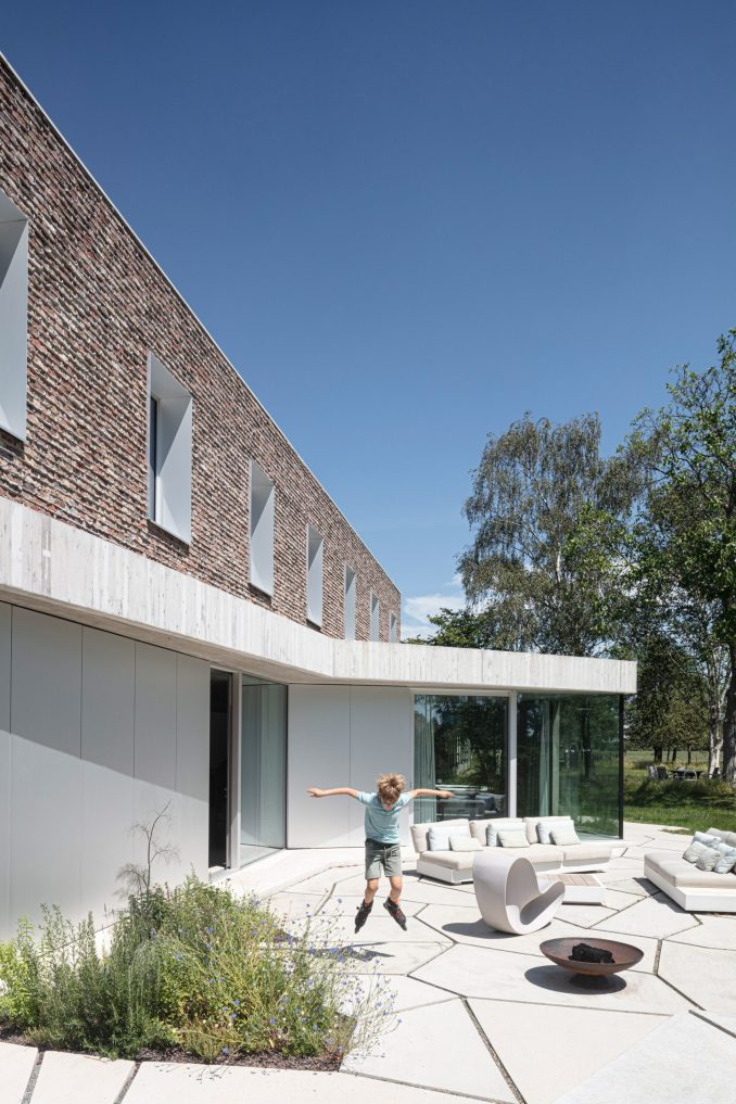 Geometric shaped paving covers the floor of the garden at House Dede