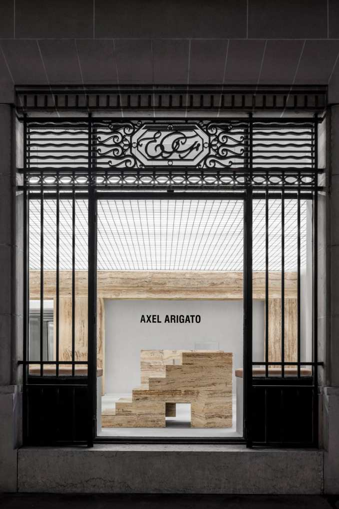 Entrance to Axel Arigato Paris store with travertine displays
