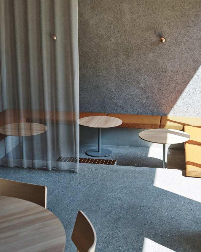 Sunken seating area with orange pillows in coffee shop by Keiji Ashizawa Design