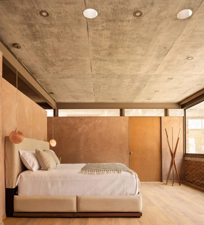 Bedroom of house in Mexico with pigmented concrete walls