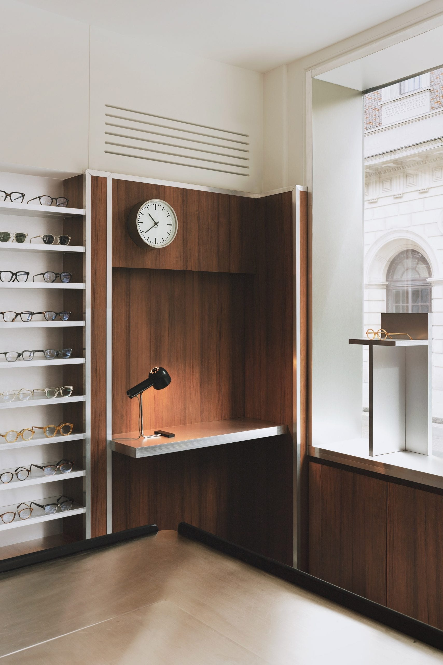 Desk nook with clock and glasses display in eyewear store by Child Studio