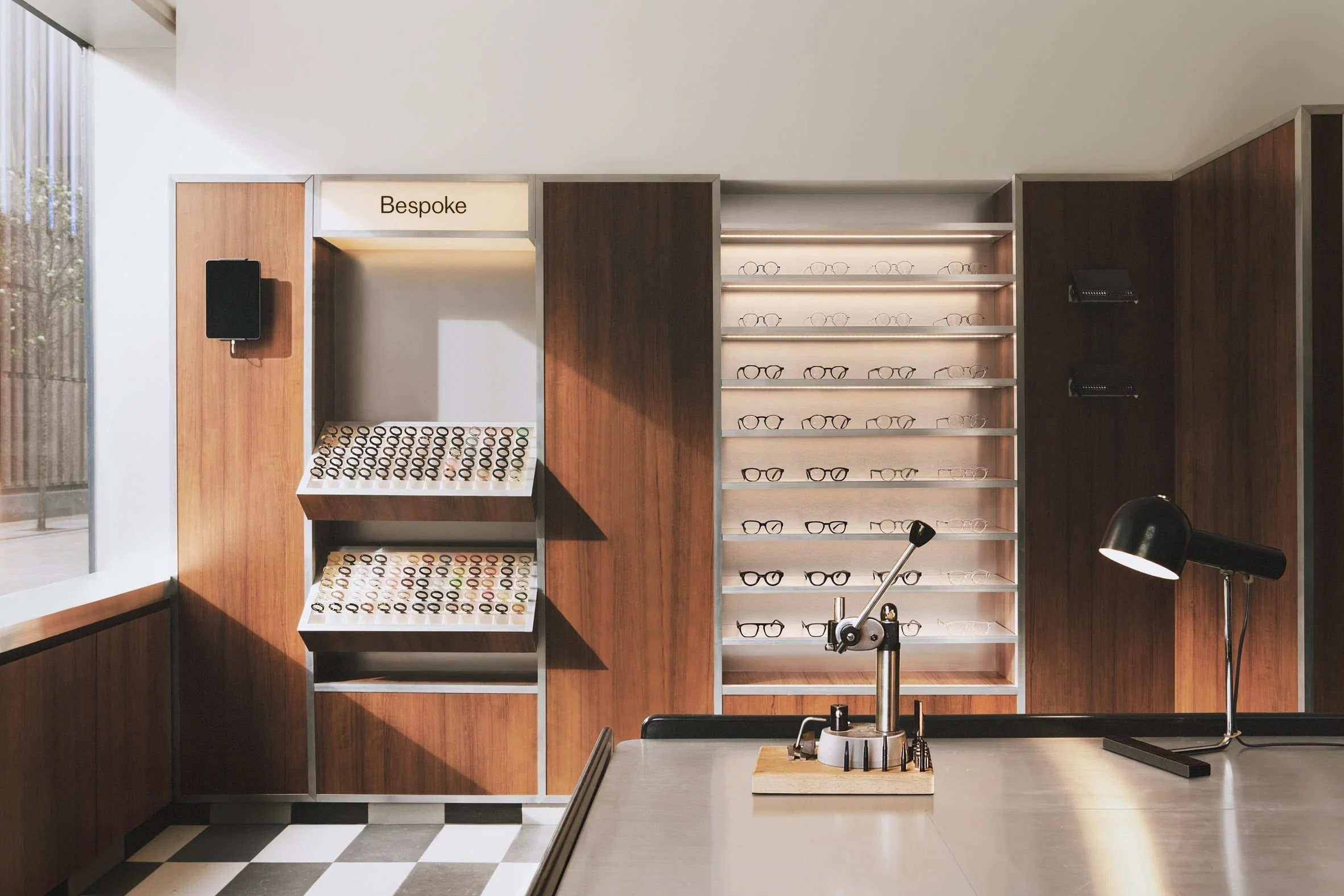 Wood-panelled walls and acrylic display stands in eyewear store by Child Studio