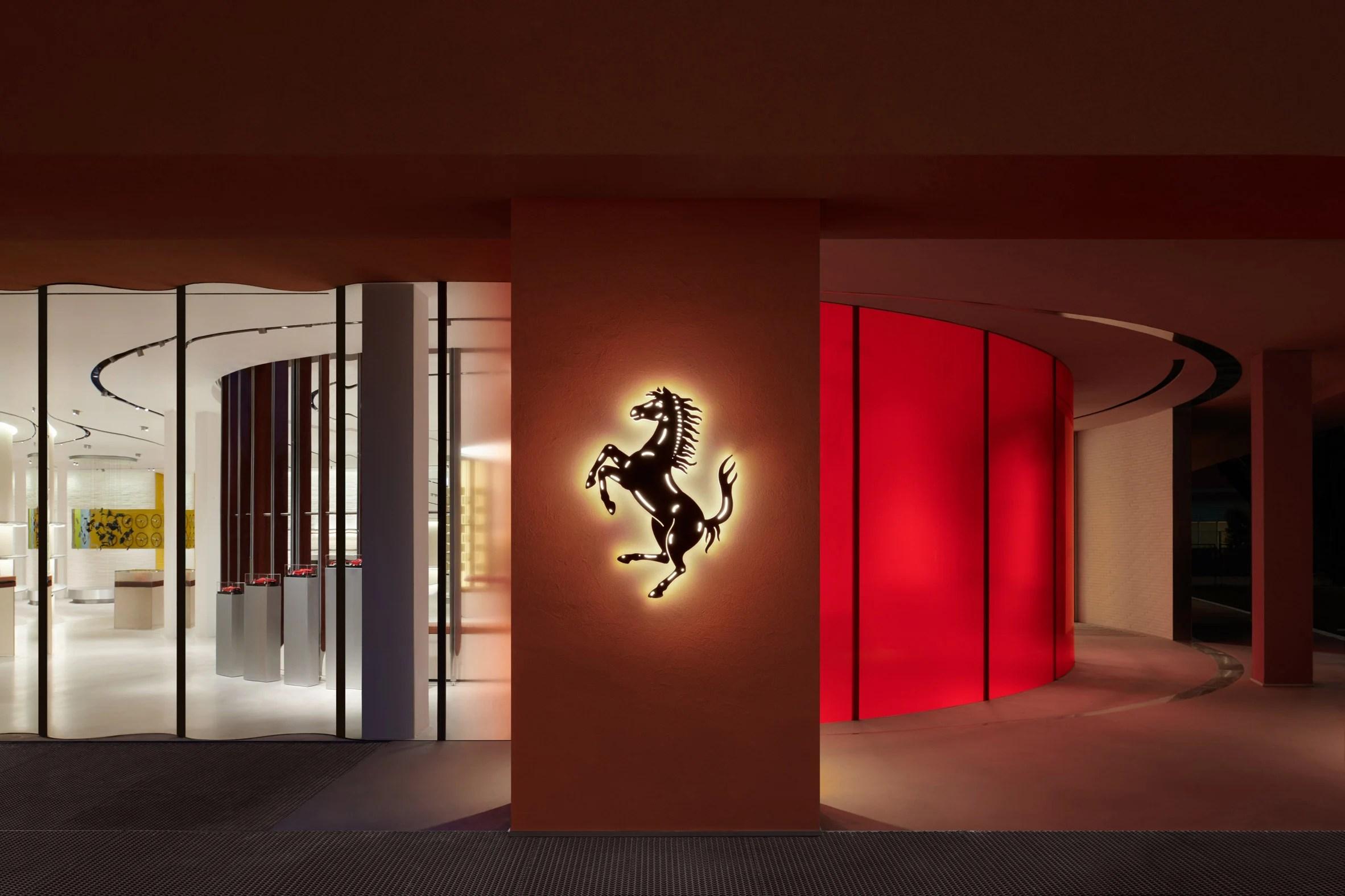 Exterior of Ferrari Maranello store with illuminated prancing horse logo
