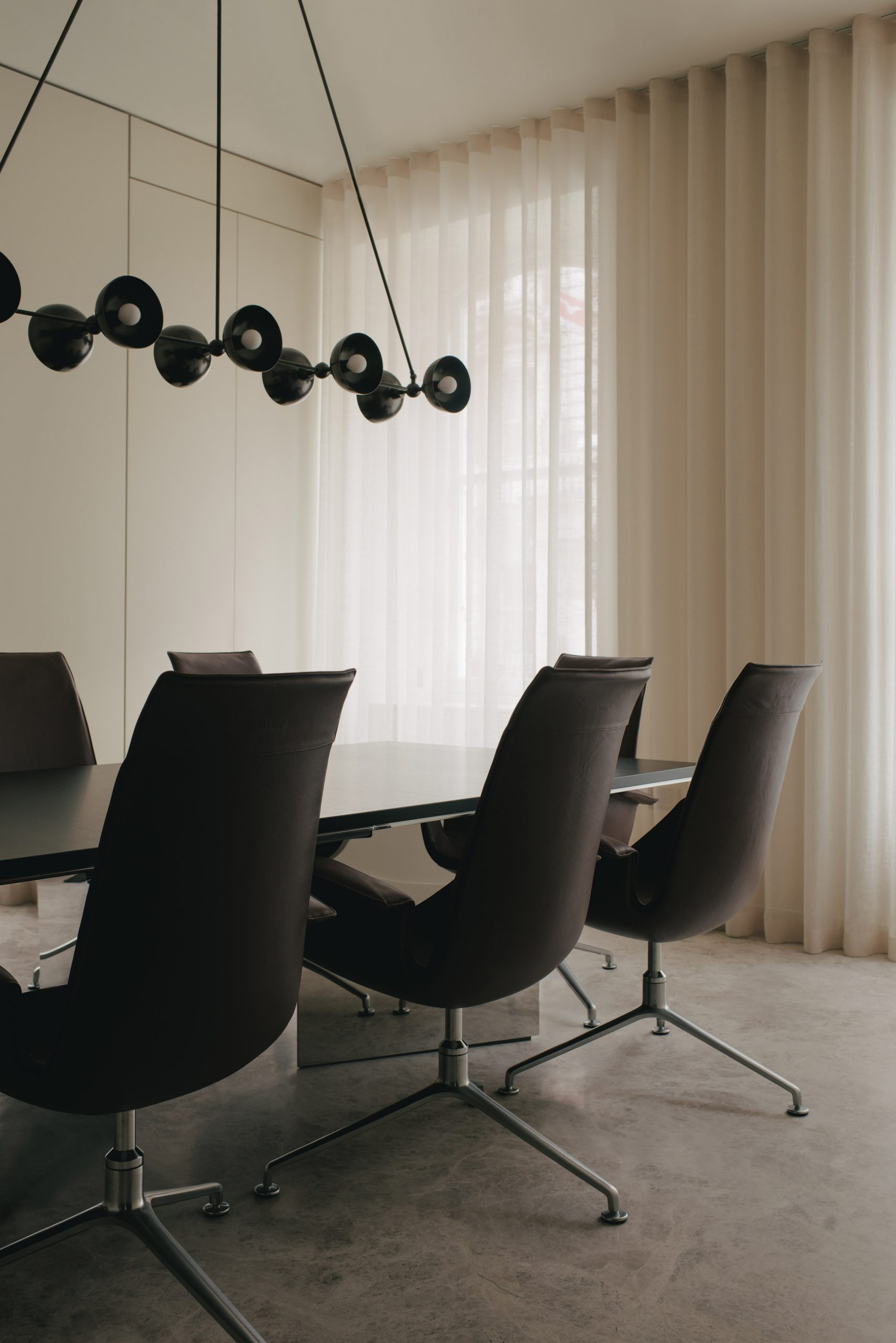 Meeting room with black chairs and large pendant lamp in Mandeville Place office