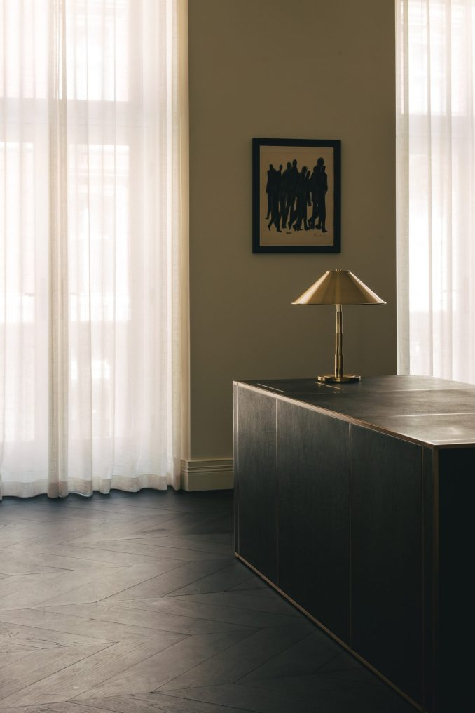 Black desk with gold lamp in Mandeville Place office