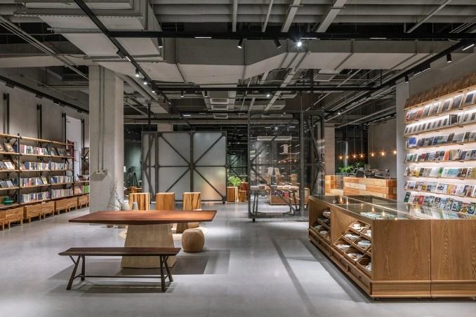 Bookshop interior by LUO Studio with wooden displays and grey floor