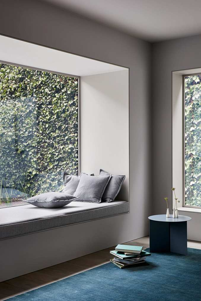 Reading nook with blue carpet and view of garden in interior by Studio Four