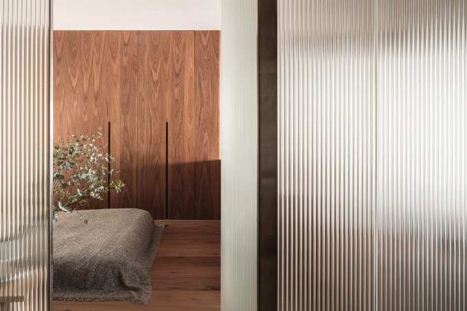 Bedroom with built-in wooden wardrobe and reeded glass partitions in interior by I IN