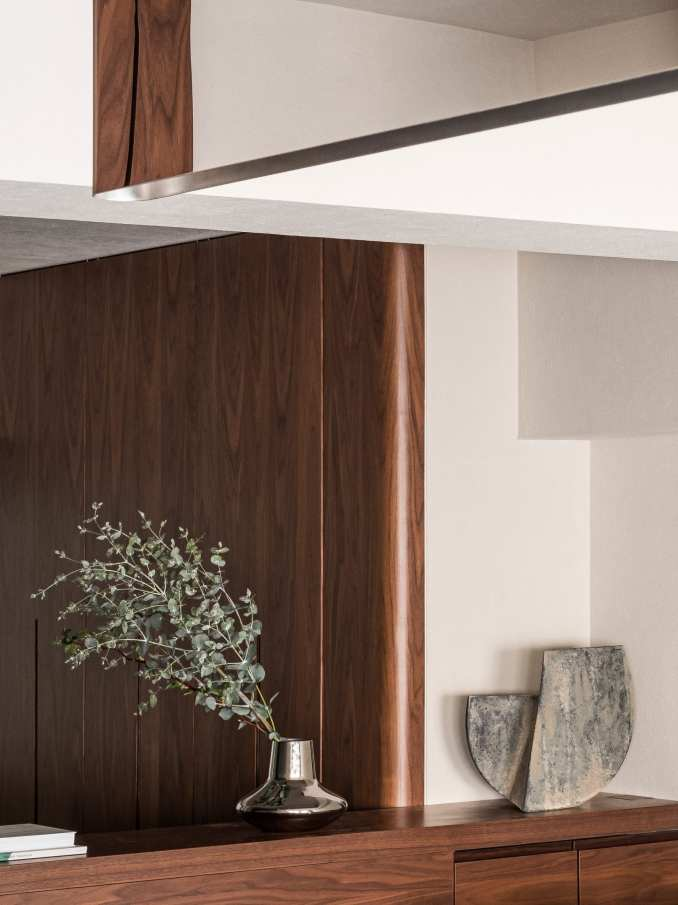 Built-in walnut wood wardrobe with decorative vase in The Life concept apartment