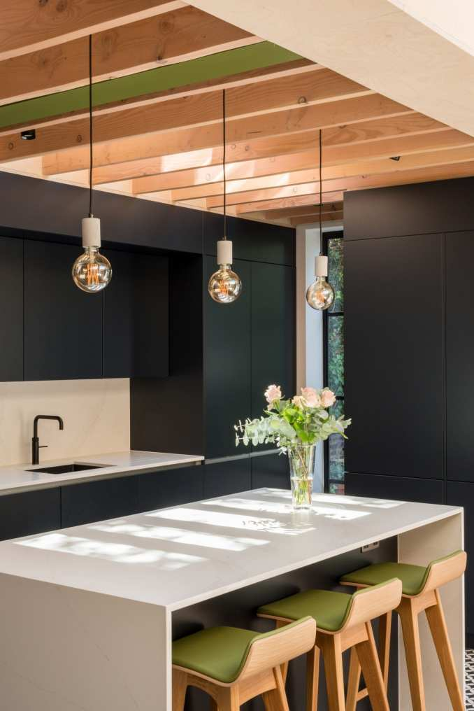 Wood beams extend over the kitchen at vault house