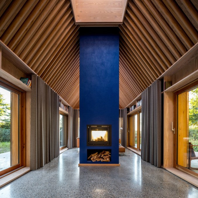 Blue hearth and timber ceiling beams inside The Author's House by Sleth