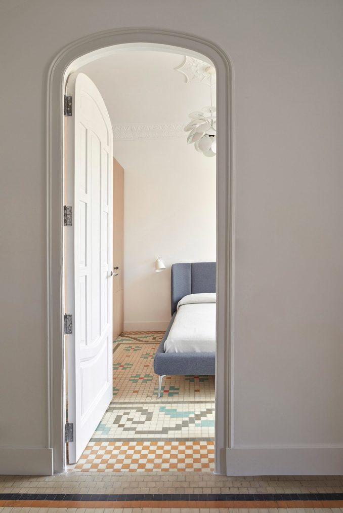 Door to bedrrom with simple blue bed and tiled mosaic floors in apartment by interior by DG Arquitecto