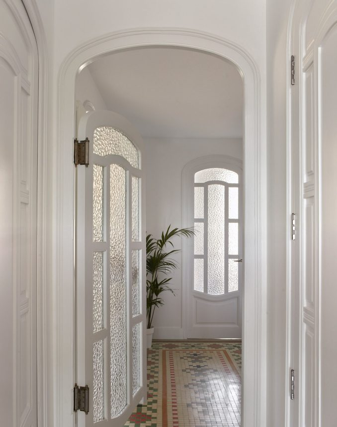 Hallway with curved wooden doors with mottled glass and mosaic floors by DG Arquitecto