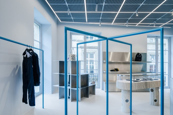 Blue clothes rails and steel displays in retail interior by AMO