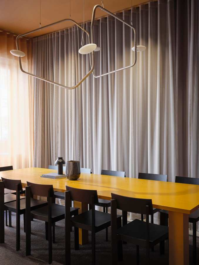 A yellow dining table was placed at the centre of the space