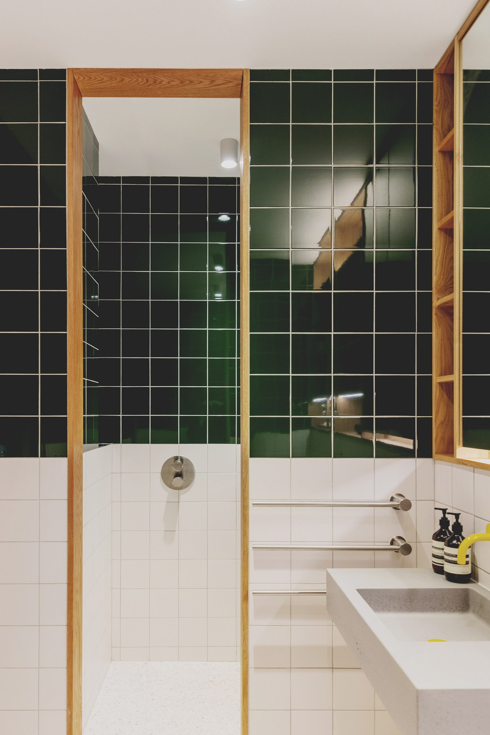 Bathroom with green and white tiles in St John Street warehouse apartment by Emil Eve Architects