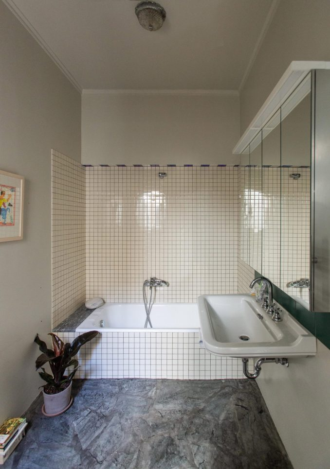 Bathroom with white tiles and marble flooring in Trikoupi apartment