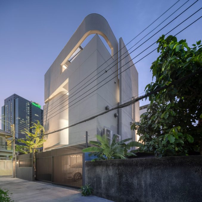 Side view of the facade of Sunset view of the exterior of 55 Sathorn house by Kuanchanok Pakavaleetorn Architects