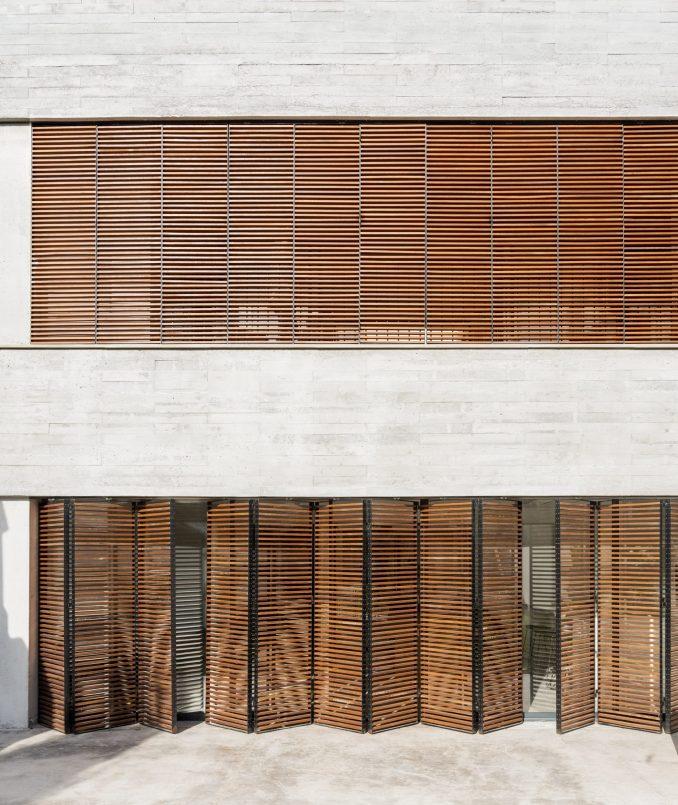 Large rectangular windows punctuate the concrete facade