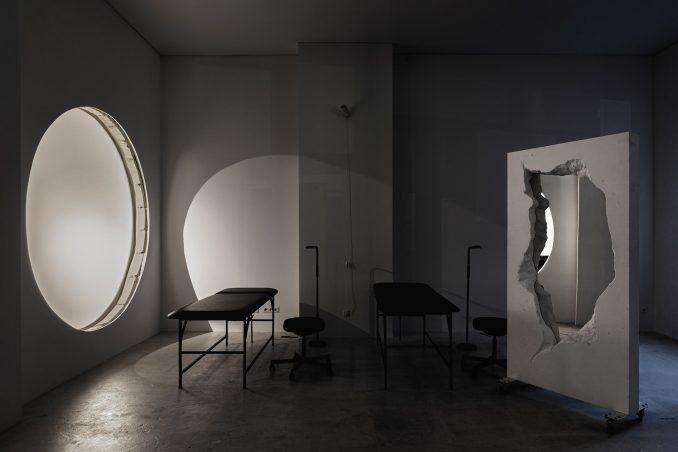 Black leather tattoo beds and mirrored partition in 6:19 Studio