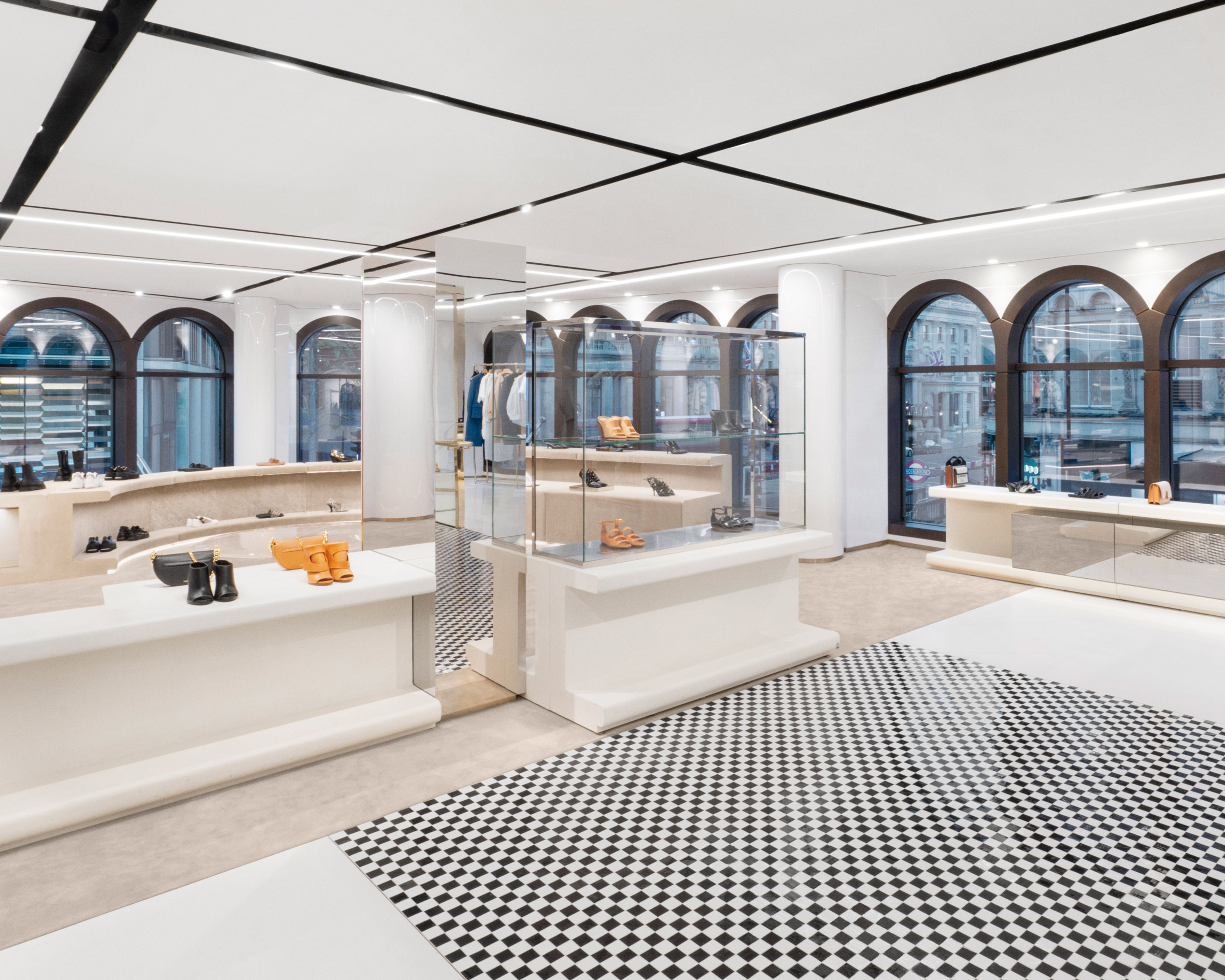 Curved shoe display and checkered floor tiles in No.1 Sloane Street by Vincenzo De Cotiis