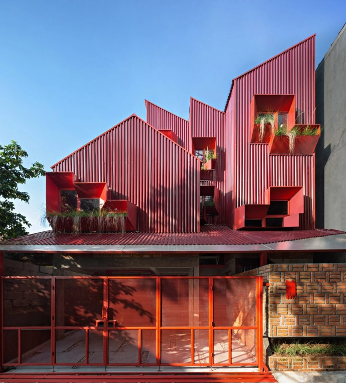 Exterior of red boarding house with shape of stacked houses