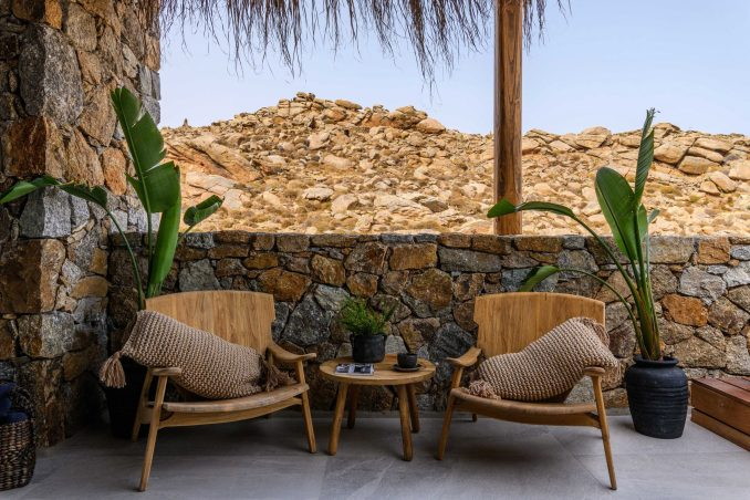 Wooden armchairs in front of stone wall of Mykonos Wellness Resort