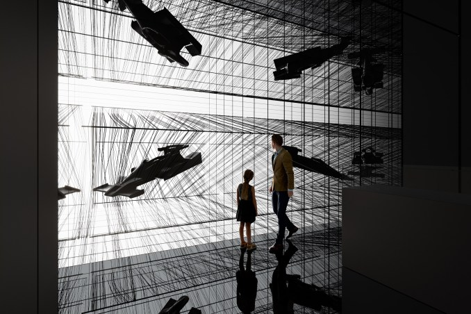 Black room with immersive installations showing carbon fibre objects