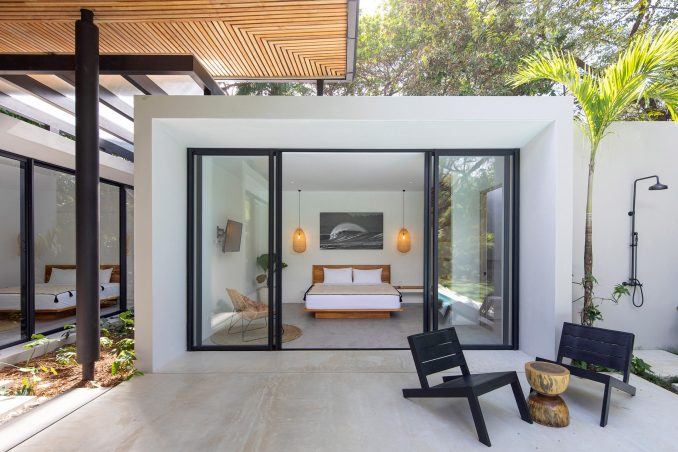 Concrete volume containing the bedroom in Naia I house with black chairs out front