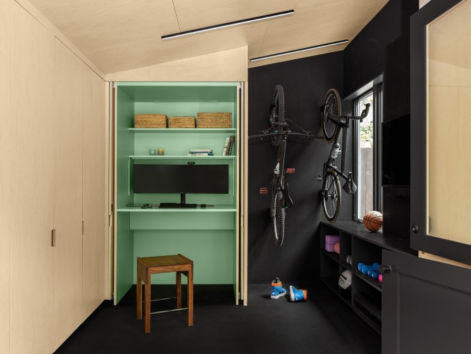 A sea-green coloured built in desk and bikes hanging on the wall