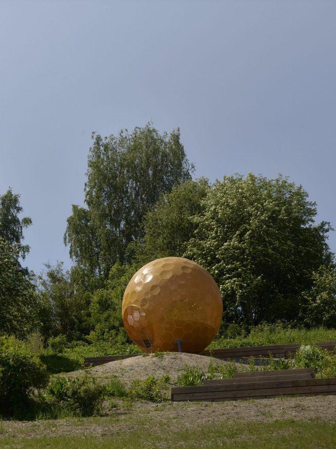 A perforated metal orange sphere at the top of the park