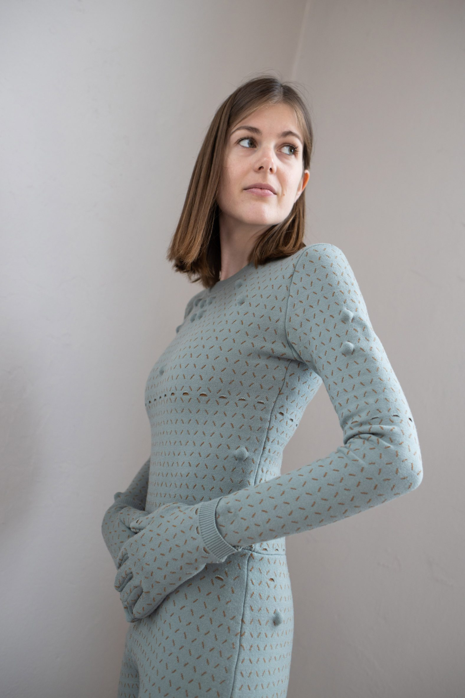 Woman wearing light teal bodysuit with matching gloves with a grid pattern stitched into it and massage balls inside the grid