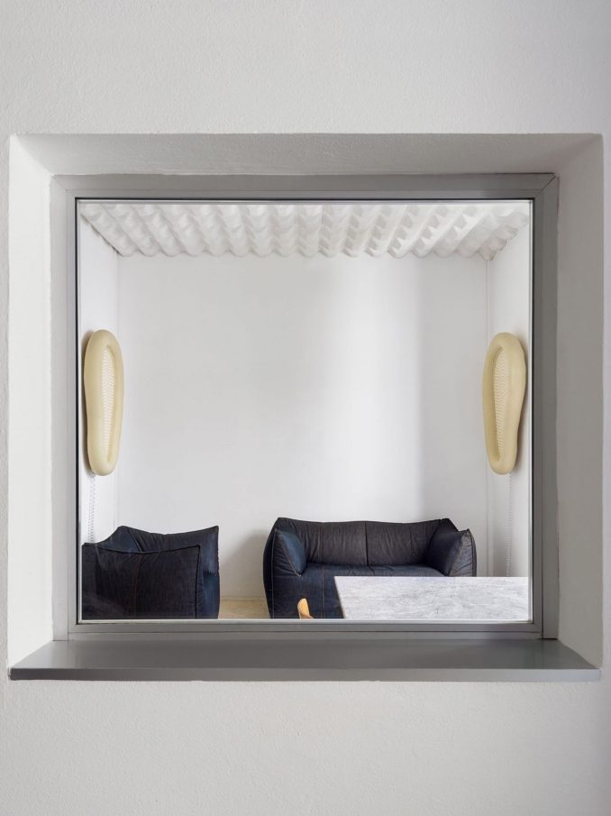 A squared window looks into a room with sofas and chairs