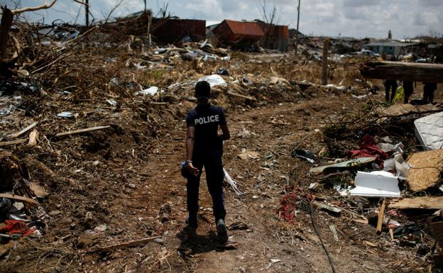 A police officer looks for victims in Abaco. / Marco Bello (Reuters)